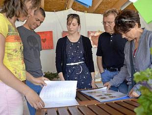 """Anne Sänger (Mitte) zeigt Besuchern ihre Skizzen. Die Lübbenerin beteiligt sich erstmals an der Veranstaltung """"Offenes Atelier"""".  Foto: Andreas Staindl"""