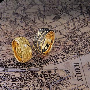 Partnerringe im Landkarten-Relief in Gelbgold mit den persönlichen Koordinaten vom Kunde von der Goldschmiede OBSESSION