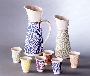 Krüge und Becher aus Porzellan in Plattentechnik mit Malerei in weiss auf farbigem Grund