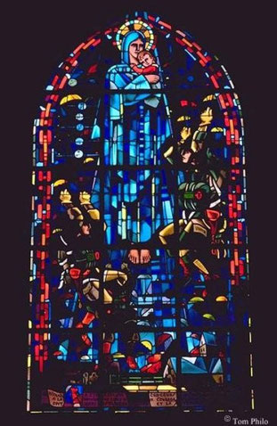 Das bekannte Kirchenfenster im Giebelhaus mit den beiden Fallschirmjägerabbildungen zu Füssen der Mutter Gottes, eine Hommage der Dorfbevölkerung an ihre Befreier.