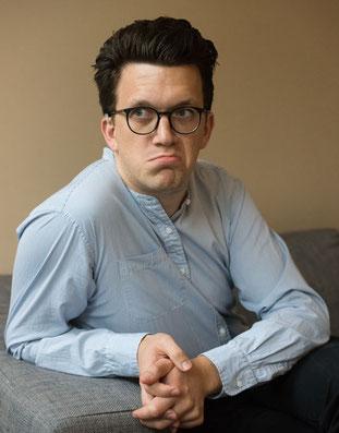Mann mit mittellangen Haaren und Brille sitzt fragend auf einer Couch.