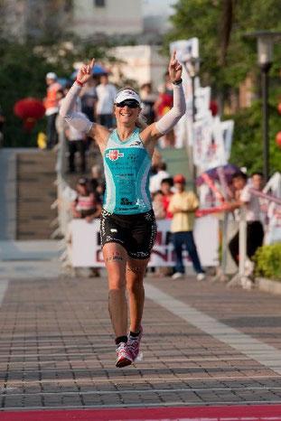 Wenige Meter vor dem Zieleinlauf als Dritte beim Ironman China, 2010.