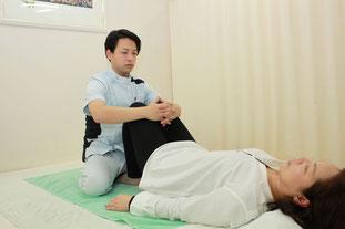 膝曲げ股関節屈曲した姿勢から下方牽引と揺らしで腰仙骨部を調整します