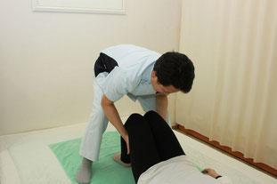 膝立姿勢で下腿牽引と揺らしを行い骨盤、腰背部から頚まで調整します