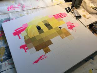 Eine im Leinwand im Prozess mit weißem Hintergrund. Liegt auf einem Schreibtisch. Im Hintergrund liegen Farben.