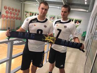 Lehmann und Tiede  stehen im Deutschlandtrikot und halten den RGC-Schal