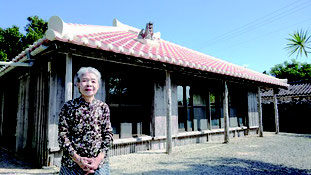 美しく葺き替えられた赤瓦屋根の大山家と大山砂子さん=1日、竹富島大山家