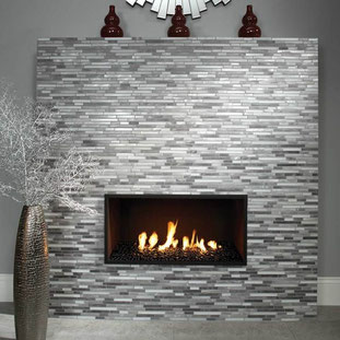 Fireplace with linear stainless steel mosaics. Three dark red vases sit on top of the fireplace. A tall, dark metallic planter is in front of the fireplace.