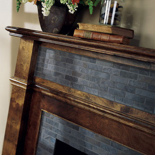 Close up of blue porcelain mosaics on a fireplace with a dark wood mantel
