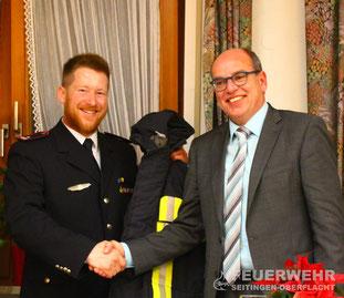 Kommandant Zepf überreicht Bürgermeister Jürgen Buhl eine Feuerwehr-Einsatzjacke als Willkommensgeschenk