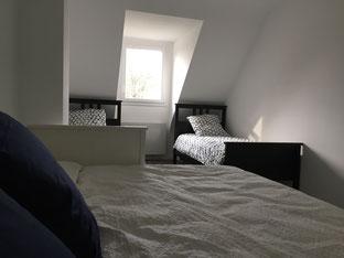 assis dans le lit divan, on peut voir les deux lits simples en face, chacun d'un côté d'une fenêtre qui se donne sur le jardin