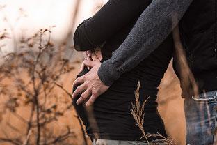 Babybauch im Profil er steht hinter Ihr und hält den Babybauch festgehalten in einer Landschaft von der Familien Fotografin Monkeyjolie