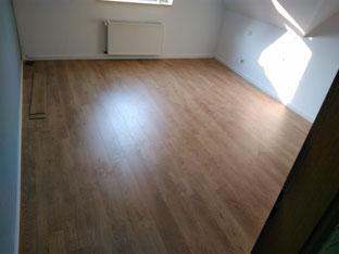30 m² Laminat Rip Oka natur und weiße Sockelleisten verlegt.