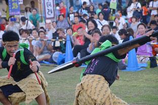 満慶太鼓10周年バージョンの中で鎌と槍を持った男性が演舞を披露した=1日夕、川平小中学校