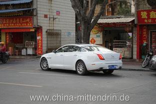 Bilderrätsel. Zwei Fragen: 1. Was macht ein Jaguar vor einem schmuddeligen Schnellrestaurant? 2. Was befindet sich im Kofferraum?