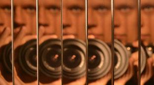 Gesicht und Photoapperat spiegeln mehreren Spiegeln