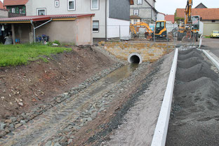 """Der mitlerweile fertig gestellte Graben in der Bachstraße. Oberhalb am """"Backhaus- Plan"""" fehlt jedoch noch sämtlicher Straßenbelag und Gehweg."""