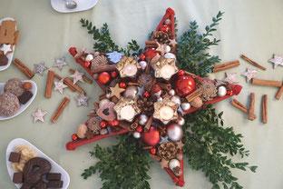 Roter Stern mir vier Teelichtern auf dem Tischdekoriert mit Zimtstangen und Gebäck.