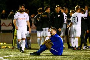 Robin Hömig nach dem Spiel niedergeschlagen während die Gäste feiern. (Foto: Deutzmann)