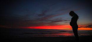Frau am Strand mit Sonnenuntergang