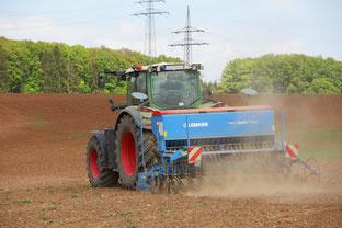 Mit einem Schlepper wird das Saatgut in den Boden gebracht