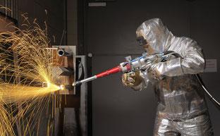 Ein Techniker im Schutzanzug zerschneidet Rohrleitungen mit dem Laserstrahl