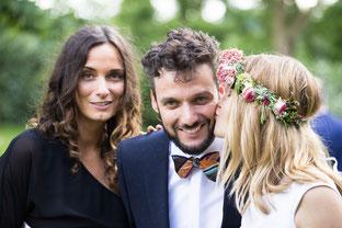 Als Hochzeitsfotograf Hanau bei der Hochzeit am Kinzigheimer Hof in Bruchköbel. Die Braut küsst den Bräutigam auf die Backe, der neben seiner Schwester steht.