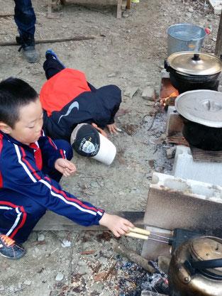 トーストを焼く柳原選手と火の管理をする岡村選手。