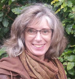 Joke Zonneveld, een stralende vrouw, lachende mond, met vol, bruin, tikje grijzend haar en groene ogen, bril, bruinejas en sjaal voor een groene beukenheg