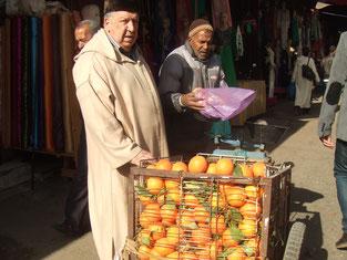 オレンジを売るおじいさん。モロッコは日本と違って野菜や果物は「計り売り」です。
