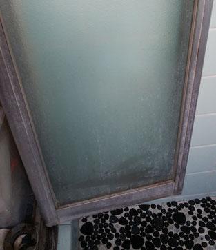 湯垢で汚れた、浴室入り口のドア