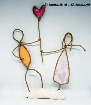 Papierdrahtfigur-Pärchen-Mann-und-Frau-halten-gemeinsam-ein-rosa-Herz