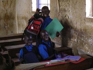新1年生3人。支援物資のバッグに大満悦のEric(9歳)とAjalo(右9歳)とAtenyo(9歳と8歳)