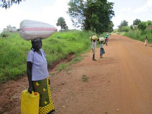 およそ20kgかと思われる袋を軽々運ぶ母娘。Acholi女子は子供でも皆な力持ち!!