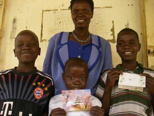 左からKinyera Eric(3), Komagum Joshua(1), Rac Kara Junior(4)の3兄妹、叔母さんと。