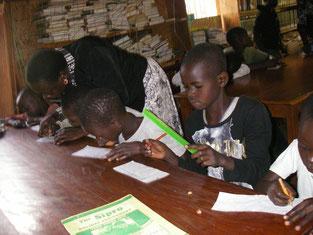"""今学期から就学した先輩たちに次いで、""""図書館塾""""で学習中の子供たち(7歳から13歳)。真剣です!"""