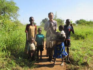 2015年3学期から就学支援する予定のOpoka Brian(後方右端)の家庭訪問時。後方左のAgeno Rwot Gladysも支援中。OgenSoのすぐ前の2人は図書館塾で学習中です。