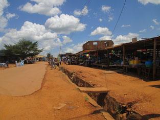 雨期でも晴れた時は眩しい青空!Kitgumタウンの中心部、マーケット通り。内戦で舗装部分が無くなった道路は、ン十年以上、ご覧の通りのままです・・・