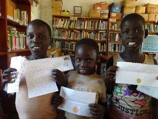 支援者の皆様からのお返事レターを手にニッコリの左からOpwonya,Nancy, Aol.