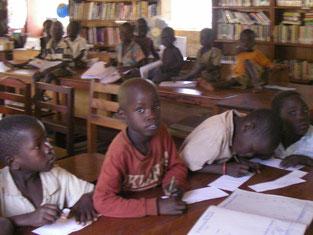 兄姉(手前左Obedi Andrew, 中Komagum Joshua)は学習中。乳幼児(後方)は、絵本(オモチャ?)を手に待ちます。寝てしまいオネショをする子も!