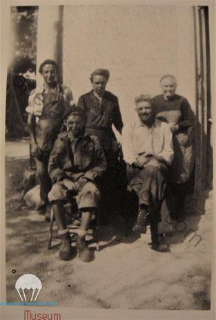 Adrien SUMIEN (en bas à droite) avec sa famille devant la ferme du pavillon, c'est ici que la 45th ID établit son bivouac et qu'il trouva la dog tag. Son fils porte une veste offerte par les alliés