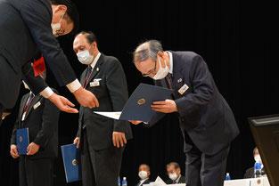 深々と頭を下げ国際会長感謝状を拝受するL.武蔵ZC