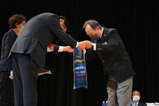 ガバナー特別賞のバナーを受取るL.樋口会長