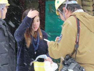 風雪吹き荒ぶ中、報道機関の記者からの取材を受け、積極的に応じる本校の生徒。