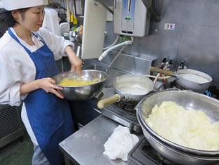 女性の職人さんです。チーズケーキを作成中です。