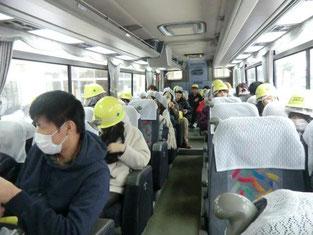 バス車中にて、危険防止の為のヘルメットを装着し、いよいよ鉱山跡への入坑を目前にした本校生徒たちの姿。