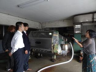 酒蔵ならではの機械を前に説明を受ける生徒たち。