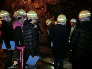 坑道内部にて、過去に鉱山で働いた経験をお持ちのボランティアガイドの方々からの説明を、真剣な眼差しで聴き入る本校の生徒たち。