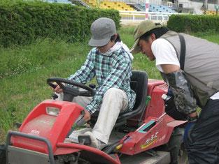 競馬場の草刈の手伝い(草刈機の使用方法の説明を聞き、自分で動かそうとしているところ)