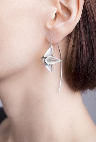 Die Ohrhänger LILL aus Silber schaukeln beim Tragen sanft hin und her und wirken dabei wie leichte Blüten im Wind. Sie faszinieren durch ihre grazile und schwerelose Ästhetik und sind tatsächlich federleicht und beim Tragen nahezu nicht zu spüren